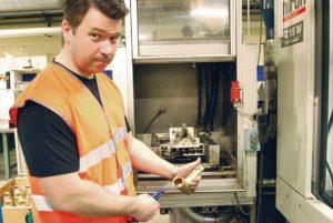Mats Nordin visar hur man innan investeringen i tvättmaskinen från LPW blåste bort spånor och torkade torrt med tryckluft vilket var en mycket krävande och tidsödande efterbearbetning för maskinoperatörerna.
