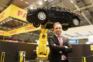 Cerold Andersson framför världens största robot, M-2300, som lockade många nyfikna mässbesökare.