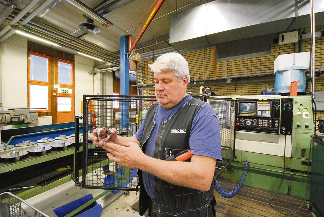 Underhållsansvarige Risto Laine visar en av närmare 30 - 40 komponenter som behövs för att tillverka en hydraulcylinder