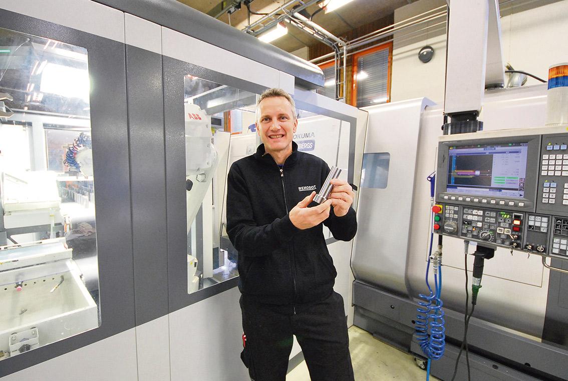 """Maskinoperatör Harri Nevalainen visar en kolv till en hydraulcylinder, tillverkad i en """"smäll""""."""