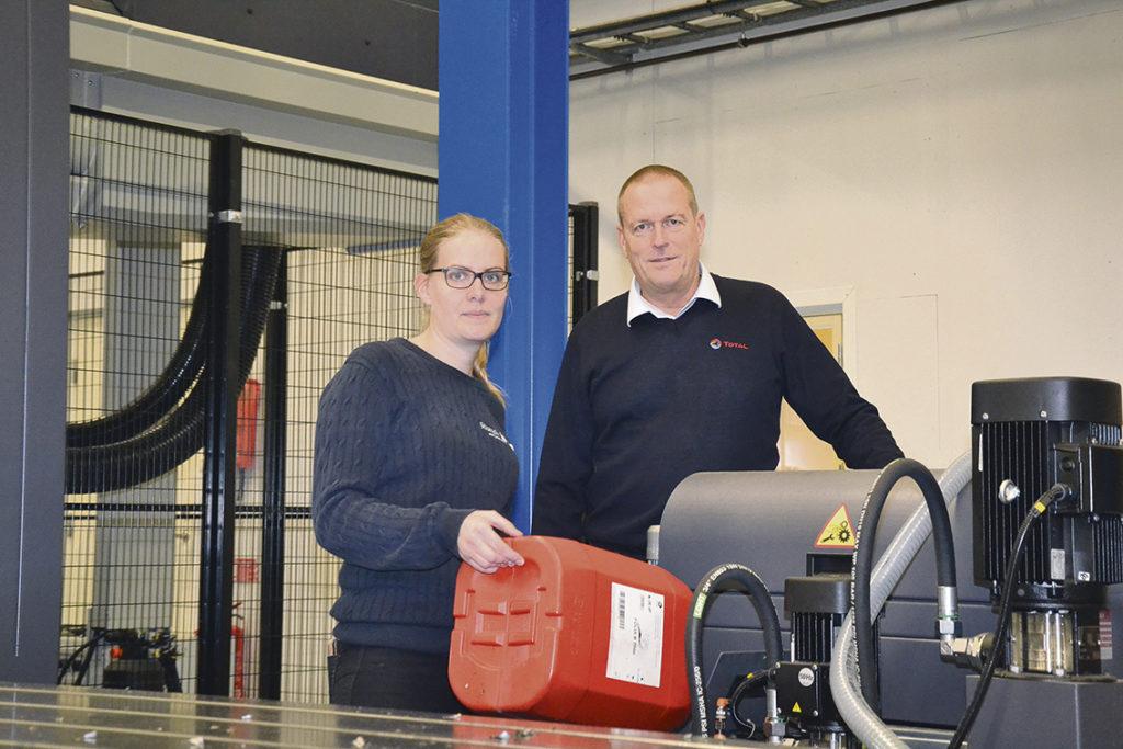 Anna Isaksson, produktionschef för Stranda och Martin Steinkamp, Total Nordic försäljningschef av industriella smörjmedel på den svenska marknaden, fyller på Total:s biopolymerbaserade vätska FOLIA i företagets nya bäddfräs BF-5200 från MTE. 0578