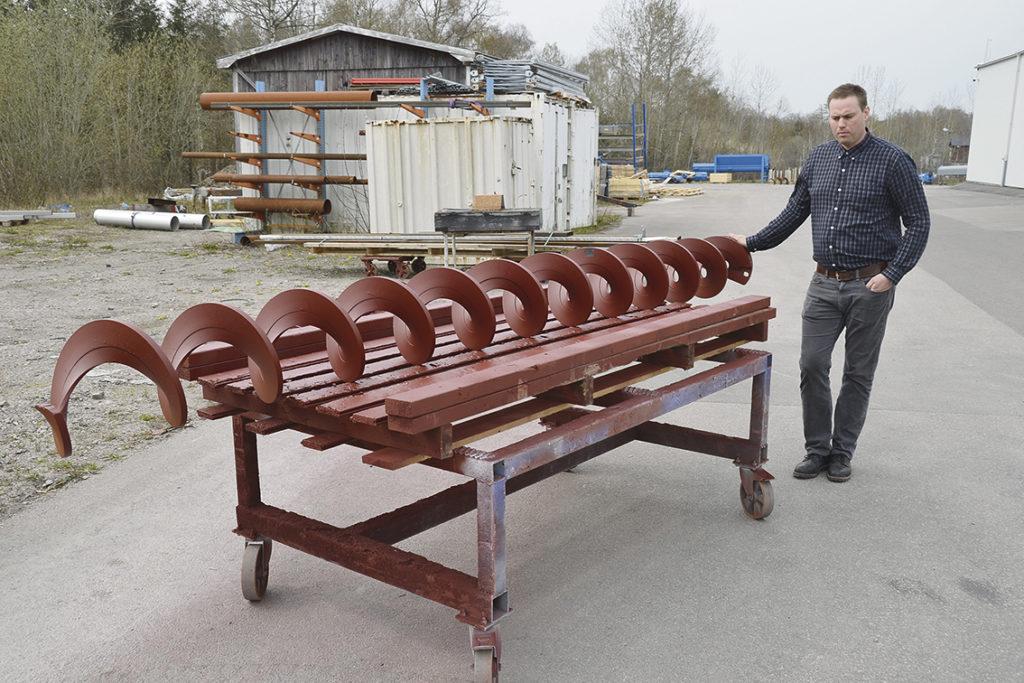 Robert Karlsson, produktionschef för PST, visar upp en typisk spiraltransportör – som inte är tillverkad med digitaliserad mätning utan är ett hantverk. Spiralen målas för transporten, och försvinner direkt när den tas i drift.