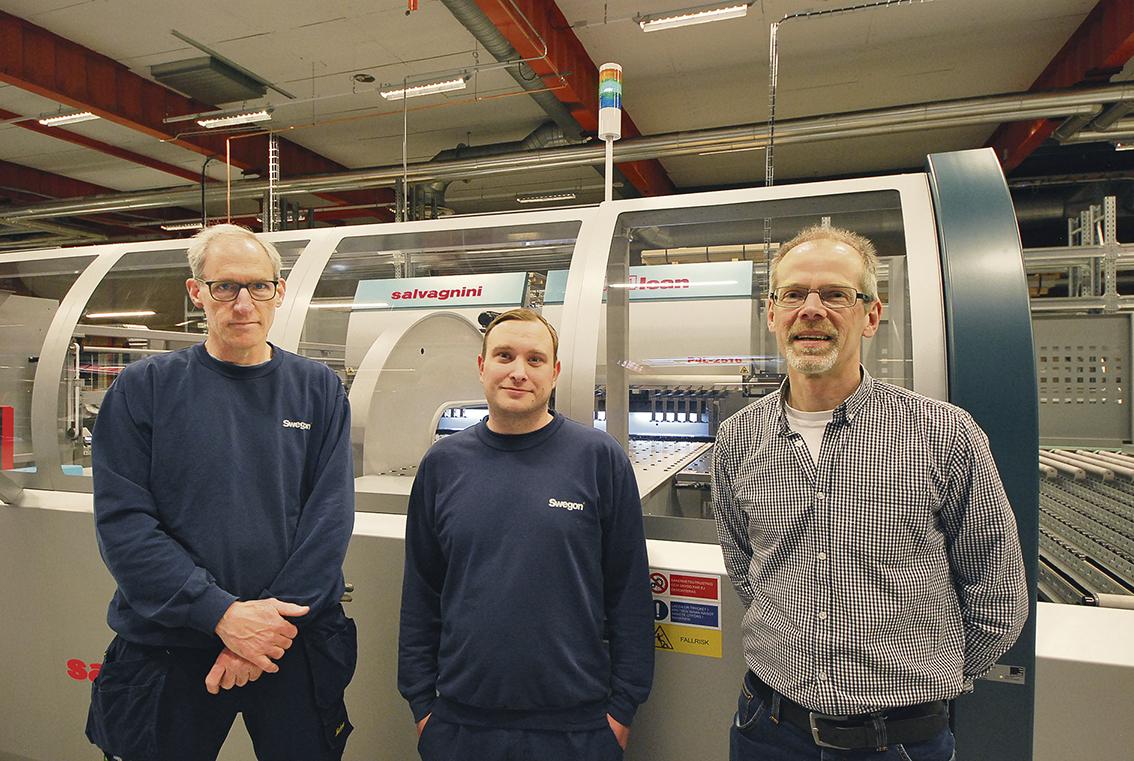 """Maskinoperatörerna John Flaminio och Alexander Augustsson har med sina erfarenheter inga problem med att sköta anläggningen. Mycket arbete är logistik med plåthantering in i de tre materialtornen och sedan ta hand om färdiga plåtar och hantera dem i ett korttidslager där panelerna i s.k. """"kit"""", går vidare till montering.  På fotot ser vi också produktionstekniker Michael Gustafsson."""