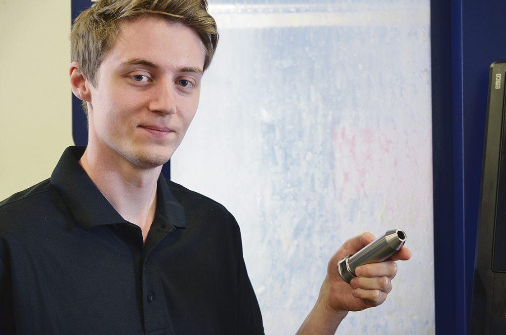 Maskinoperatören Jonathan Ekström visar en detalj där Hellstens använder det nya verktyget LOGIQ3CHAM, ISCAR´s löstoppsborr med 3 effektiva skäreggar.
